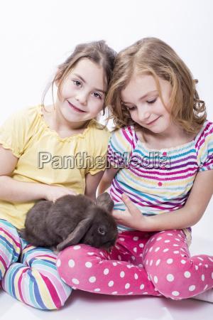 bambina seduta con il coniglietto sorridente