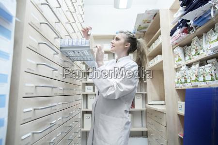 giovane farmacista in farmacia scegliendo farmaci