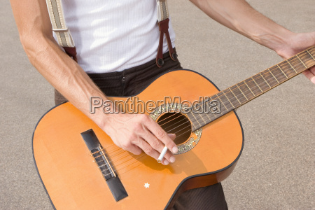 man playing guitar mid section