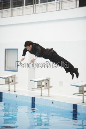 uomo daffari che salta in piscina