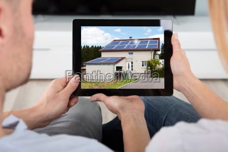couple looking at house with digital