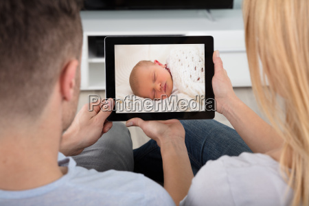 couple looking at baby on digital