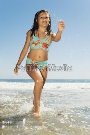 teenage, girl, running, on, beach - 21396037