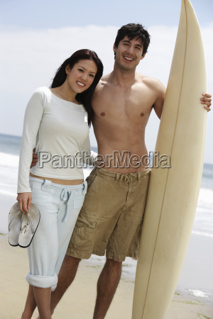 couple, with, surfboard, on, beach - 21404333