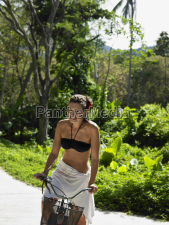donna in bikini top riding bicicletta