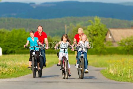 famiglia con i bambini che ciclano
