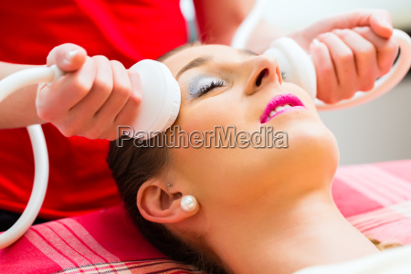 woman having face massage in wellness