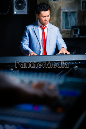 asian keyboarder playing in recording studio