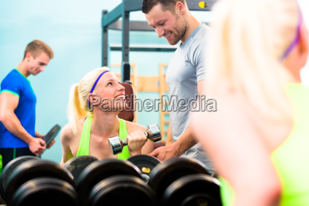 woman in gym training with dumb