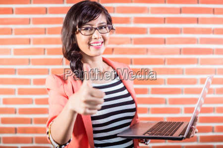 asian college student with laptop showing
