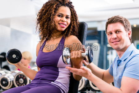 african woman and trainer at exercise