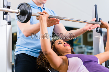 black woman with trainer lifting weights