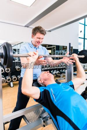 trainer assisting senior man lifting barbell