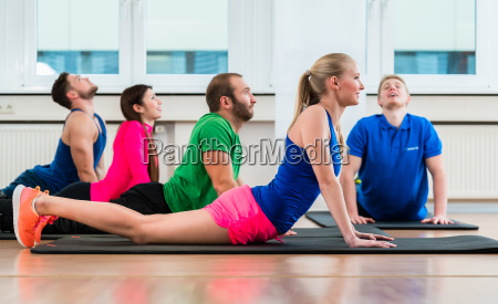 recreational athletes doing yoga exercises in