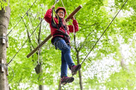bambino che raggiunge la piattaforma arrampicata