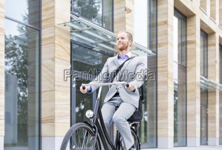 uomo daffari sorridente in bicicletta fuori
