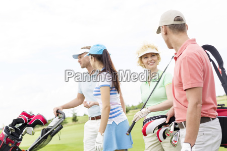 friends talking while walking at golf