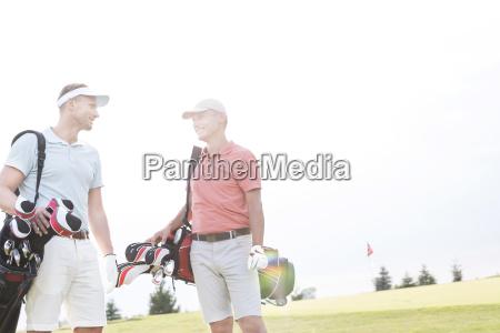 smiling men talking at golf course