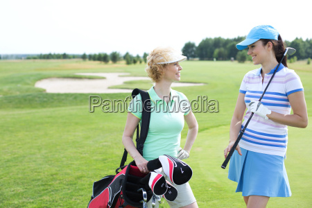 smiling female golfers talking at golf