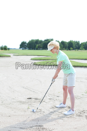 middle aged woman playing golf at