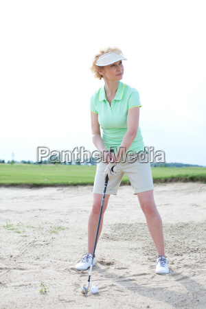 woman playing golf at course against