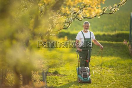 anziano falciare prato suo giardino fuoco