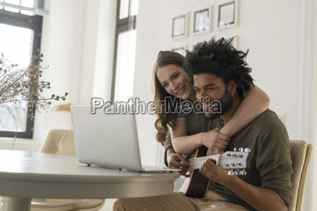 smiling couple in front of laptop