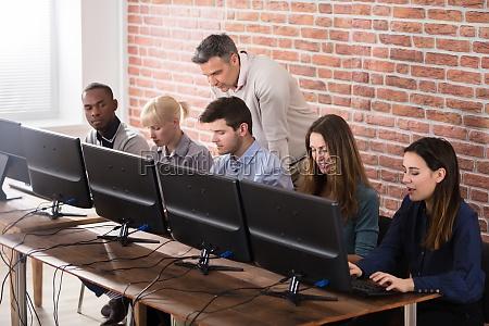 student with teacher in computer school