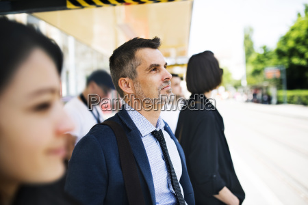 businessman waiting at the bus stop