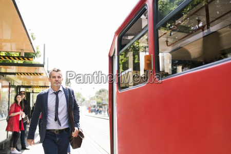 businessman trying to catch the tram