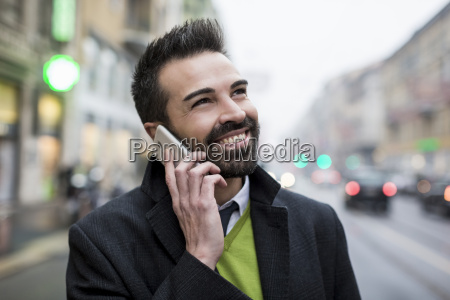 smiling businessman in the city on