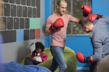 colleagues boxing in office lounge