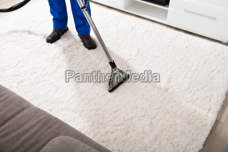 janitor cleaning carpet with vacuum cleaner