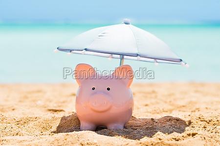 salvadanaio sotto il ombrellone in spiaggia