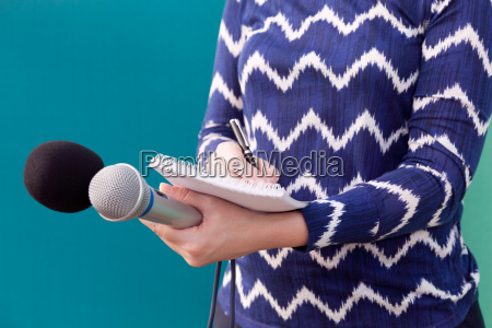 female journalist at press conference writing
