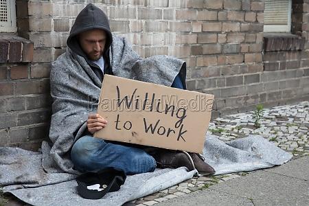 luomo senzatetto che tiene il cartone
