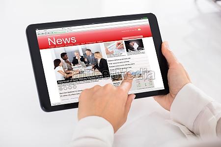 persona che legge notizie su tablet