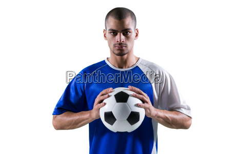 portrait of football player holding football