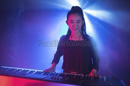 female musician playing piano in illuminated