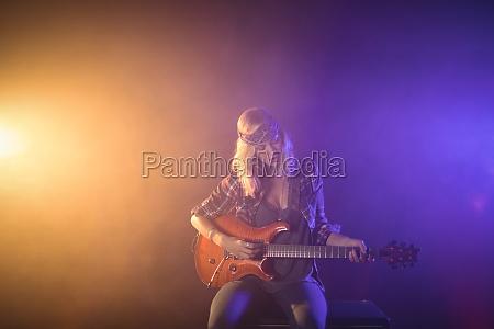 female guitarist performing in illuminated nightclub