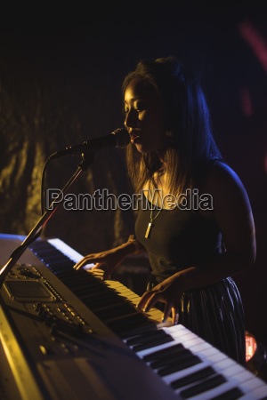 confident female playing piano while singing