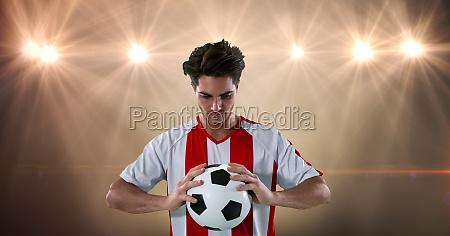 soccer player holding ball at illuminated