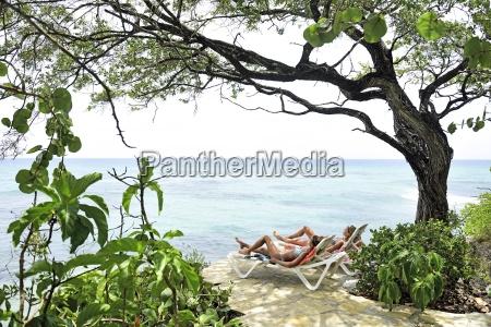 two women relaxing on sun loungers