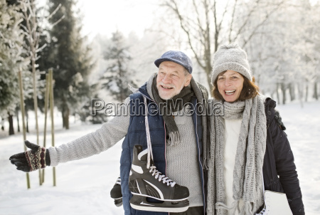 happy senior couple with ice skates