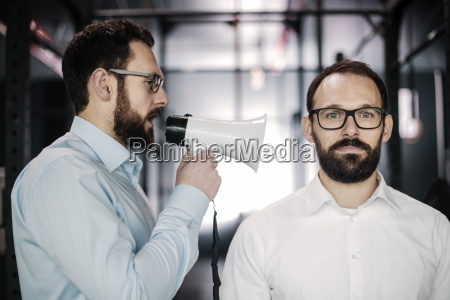manager with megaphone giving businessman orders