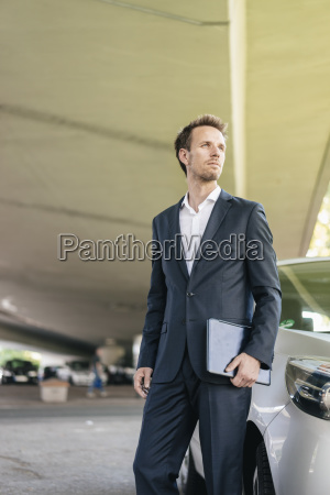 businessman standing next to car holding