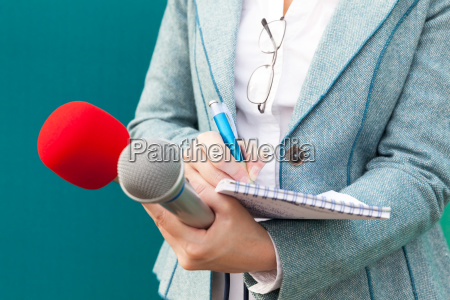 female reporter taking notes at news