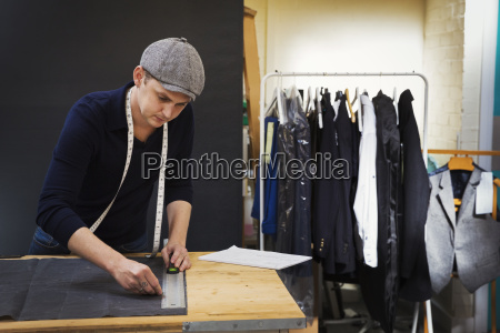 a man at a workbench measuring