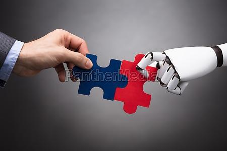 uomo daffari e robot tenendo puzzle