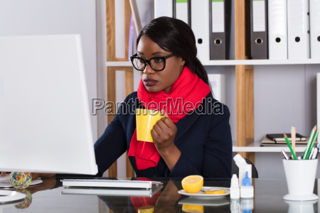 woman working on computer with cup
